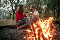 被迷恋的夫妇并且微笑坐野餐在篝火的f森林里 免版税库存图片