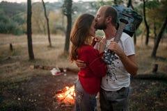 被迷恋的夫妇站立与吉他,拥抱和亲吻反对后面 免版税库存照片