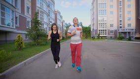 被迷恋的配偶带领在体育衣服、在城市环境里和他的妻子的一种活跃生活方式跑的一个成人人 影视素材