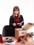 被遣散的女孩在办公室投入个人财产 免版税图库摄影