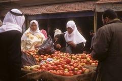 被遮掩的阿拉伯妇女在街市上采购苹果 免版税库存图片
