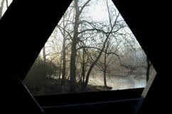 从被遮盖的桥的内部窗口视图在农村河和森林 图库摄影