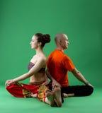 被配对的瑜伽训练在演播室,绿色背景的 图库摄影