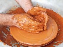 被采取的陶瓷工手在瓦器轮子的特写镜头 免版税图库摄影