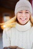 被钩的帽子的俏丽的女孩在她手和微笑上的拿着闪烁发光物室外 免版税库存图片