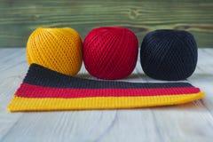 被钩编编织物的全国德国旗子,被编织的样式 毛线三个球在德国旗子颜色的 免版税库存照片