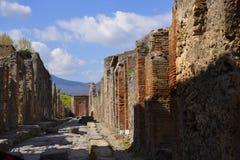 被铺的街道在一次被埋没的罗马市在那不勒斯南部的庞贝城在维苏威火山阴影笼罩下 免版税库存图片