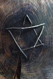 被锤击的导线大卫王之星集合到被烧焦的木刻里的面孔 库存照片