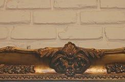 被镀金的装饰画框上面对一个被绘的砖墙 免版税图库摄影