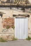 被镀锌的板料阻碍的老被放弃的修造的门 免版税库存图片
