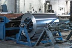 被镀锌的钢片卷在切割机的、铁器和金属制品制造业工厂、生产金属管子和管 库存照片