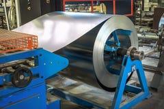被镀锌的钢片卷在切割机的、铁器和金属制品制造业工厂、生产金属管子和管 免版税库存图片
