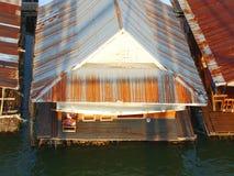 被镀锌的铁山墙,游艇在河 库存图片