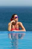 被镀青铜的秀丽。游泳池边女孩。红色的妇女 免版税图库摄影