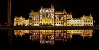 被阐明的布达佩斯议会在匈牙利在晚上,从另一异常的边的看法 免版税库存照片