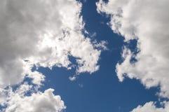 被阐明的蓬松白色云彩后面明亮地点燃了,蓝天 免版税库存照片