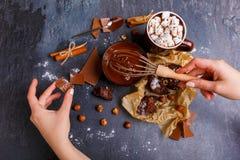 被阻碍的手熔化了巧克力用榛子,在另一只手上每巧克力片断  免版税库存照片