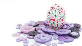 被隔绝的复活节快乐,五颜六色的复活节彩蛋站立在紫色按钮的,复活节假日装饰,复活节概念背景 免版税库存照片