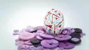 被隔绝的复活节快乐,五颜六色的复活节彩蛋站立在紫色按钮的,复活节假日装饰,复活节概念背景 库存照片
