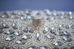 被隔绝的小珠和假钻石装饰了有她的婚礼乐队的传动器,在一块蓝色绒面革皮革布料 图库摄影