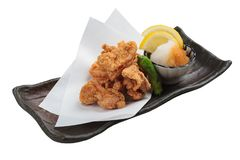 被隔绝的日语油炸了与烹调纸的Karaage服务与天麸罗调味汁Tentsuyu混合剁碎萝卜的鸡 免版税库存图片