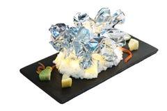 被隔绝的燃烧由箔,与盐的烧伤烤了蛤蜊套服务与在黑长方形板材的被切的石灰在washi 库存图片