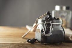 被隔绝的黑橄榄,金属螺盖玻璃瓶,木背景 Mediteranian食物 r 免版税库存图片