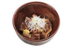 被隔绝的Nikujaga包括牛肉,土豆和萝卜炖顶部用切的萝卜和薤在棕色陶瓷碗 免版税库存图片