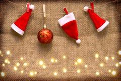 被隔绝的三个圣诞老人帽子和红色圣诞节球 免版税库存照片