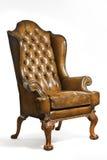 被隔绝的古色古香的皮革翼状靠背椅被雕刻的腿 库存照片