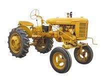 被隔绝的古色古香的黄色拖拉机 免版税库存图片