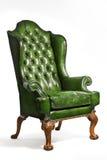 被隔绝的古色古香的绿色皮革翼状靠背椅被雕刻的腿 库存照片