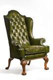 被隔绝的古色古香的绿色皮革翼状靠背椅被雕刻的腿 免版税库存图片