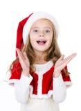 被隔绝的圣诞老人帽子的惊奇的逗人喜爱的小女孩 免版税库存照片
