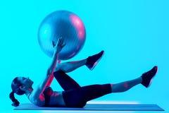 被隔绝的妇女exercsing的健身pilates exercices 免版税库存图片