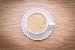被隔绝的杯子在木桌上的牛奶咖啡 免版税库存图片