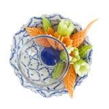 被隔绝的泰国雕刻的菜旁边圆盘在白色装饰 库存图片