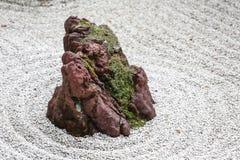 被隔绝的石头在有白色沙子和青苔的日本禅宗庭院里 免版税库存图片