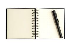 黑被隔绝的笔和空白的笔记本 库存图片