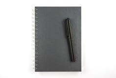 黑被隔绝的笔和空白的笔记本 库存照片