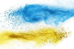 被隔绝的蓝色和黄色粉末爆炸 免版税图库摄影