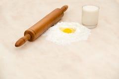 被隔绝的蛋牛奶和小麦面粉与路辗在大理石桌上 免版税库存图片