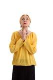 被隔绝的年长妇女祈祷 免版税库存图片