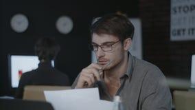 被集中的企业分析家观看的文件和膝上型计算机屏幕在黑暗的办公室 股票视频