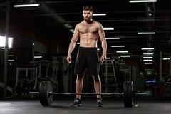 被集中的体育人做与杠铃的体育锻炼 免版税图库摄影