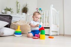 被集中的可爱的小孩男孩坐地板和修造的玩具塔 免版税图库摄影