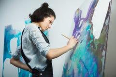被集中的女孩集中于在艺术疗法的创造性的艺术做过程 免版税图库摄影