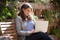 被集中的女实业家与在长凳的膝上型计算机一起使用 免版税库存图片