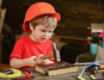 被集中的孩子与锤子一起使用 获取新的技能的小男孩 学会的学龄前儿童锤击钉子 库存图片