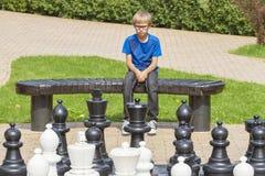 被集中的孩子,考虑他的接下来的步骤,坐一个长木凳在一场室外下棋比赛期间使用与原物一样大小片断a 免版税图库摄影